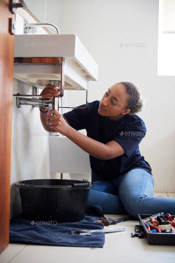 Female Plumber Working To Fix Leaking Sink In Home Bathroom