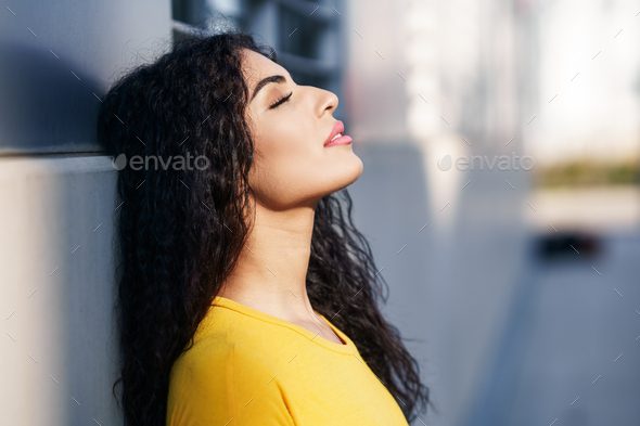 Arab woman with eyes closed in urban background - Stock Photo - Images