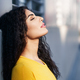 Arab woman with eyes closed in urban background - PhotoDune Item for Sale