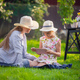 Happy mother and her little daughter enjoying free time using tablet computer while relaxing on - PhotoDune Item for Sale
