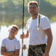Such a small fish. Father and son stretching a fishing rod with fish on the hook while little boy - PhotoDune Item for Sale