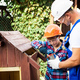 Young teenager boy and his father in caps painting wooden dog house together on sunny day at - PhotoDune Item for Sale