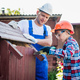 Handsome teenage carpenter and his father in protective glasses are smiling while working with wood - PhotoDune Item for Sale