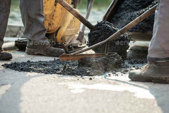 Two construction workers patching bump in the road - Stock Photo - Images
