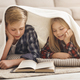 Brother And Sister Reading Book Covered With Blanket At Home - PhotoDune Item for Sale