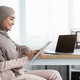 Smiling Islamic Businesswoman Using Digital Tablet While Sitting At Workplace - PhotoDune Item for Sale