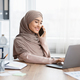 Young Arabic Businesswoman Talking On Cellphone And Using Laptop In Office - PhotoDune Item for Sale
