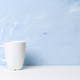 White mug with tea or coffee on a white table opposite a light blue concrete wall. - PhotoDune Item for Sale