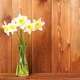 Bouquet of fresh flowers, daffodils in vase on wooden table, opposite brown wooden wall - PhotoDune Item for Sale