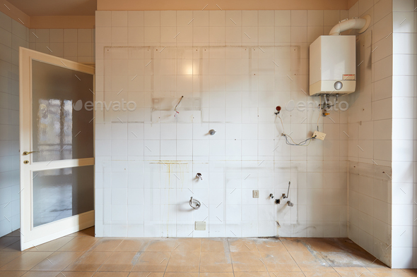 Old, empty kitchen wall with white, dirty tiles in apartment interior - Stock Photo - Images