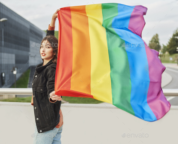 Portrait of young woman with rainbow flag - Stock Photo - Images