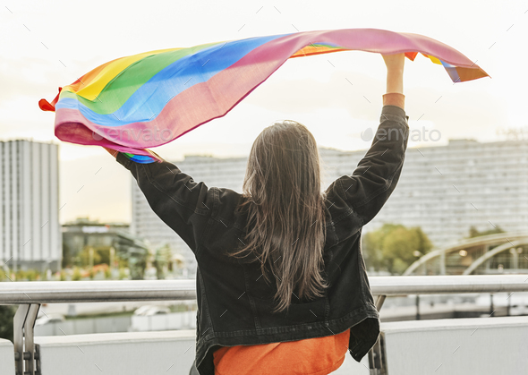 Rear view of young woman waving rainbow flag - Stock Photo - Images