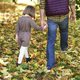 Rear view of child and father walking in autumn woods - PhotoDune Item for Sale