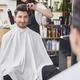 Smiling male customer sitting in hair salon - PhotoDune Item for Sale