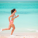 Fit young woman doing exercises on tropical white beach in her sportswear - PhotoDune Item for Sale