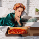 young female with finger near lips with pizza box pizza in bed - PhotoDune Item for Sale