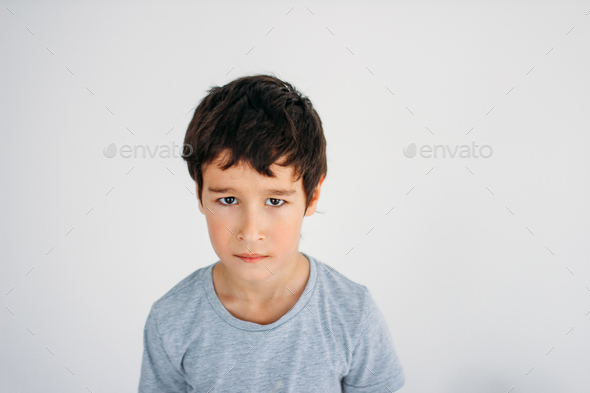 Frustrated Moody tween boy looking at camera on white background - Stock Photo - Images