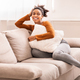 Relaxed Afro Lady Sitting On Couch Hugging Pillow Indoor - PhotoDune Item for Sale
