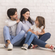 Affectionate Young Family Bonding Together While Sitting On Floor At Home - PhotoDune Item for Sale