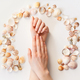 Woman's hands with perfect manicure and seashells frame. Top view photo isolated on white, flat lay - PhotoDune Item for Sale