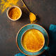 Top down view of turmeric latte cup on a textured dark background. - PhotoDune Item for Sale