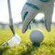 Hand in glove placing golf ball on tee - PhotoDune Item for Sale