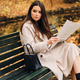 Beautiful stylish brunette girl with newspaper resting on bench in autumn park - PhotoDune Item for Sale