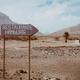 Old signpost in abandoned barren desert scenery. Volcano rugged on the horizon. Sao Vicente Cape - PhotoDune Item for Sale