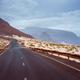 Asphalt road leads between black volcano erosion mountain and white sand dunes. Breathtaking - PhotoDune Item for Sale