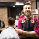 Portrait of happy young barber with client at barbershop and smiling - PhotoDune Item for Sale