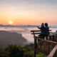 Young couple traveler looking at sea of mist and sunset over the mountain at Mae Hong Son, Thailand - PhotoDune Item for Sale