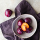 Top view of purple plum in a ceramic bowl on a beige textured background. - PhotoDune Item for Sale