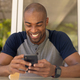 Young man smiling while using his mobile phone - PhotoDune Item for Sale