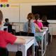 Group of schoolchildren sitting at desks in an elementary school classroom - PhotoDune Item for Sale