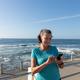 Female jogger using mobile phone on seaside - PhotoDune Item for Sale