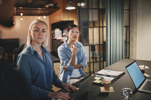 Businesswomen talking with coworkers during an office meeting - Stock Photo - Images