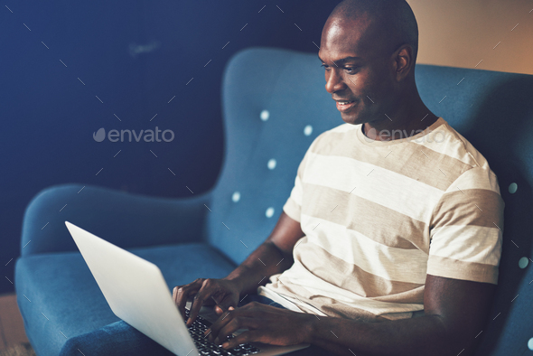 Smiling African entrepreneur sitting on a  couch working online - Stock Photo - Images