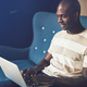 Smiling African entrepreneur sitting on a  couch working online - PhotoDune Item for Sale