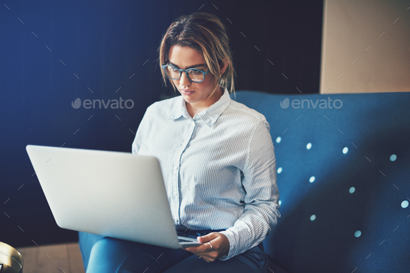 Young businesswoman sitting on a sofa working online - Stock Photo - Images