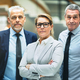 Confident mature businesswoman and two colleagues standing in an office - PhotoDune Item for Sale