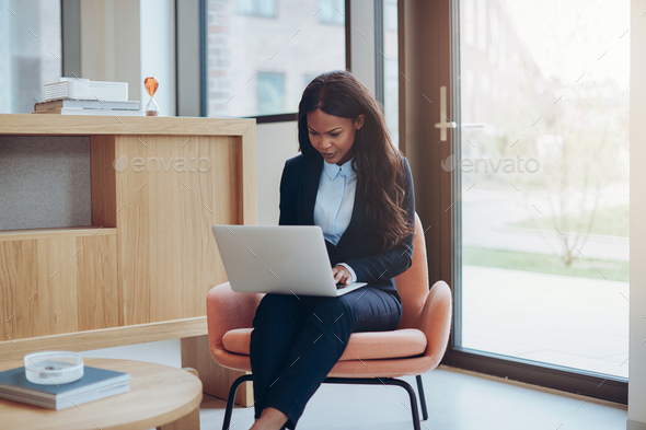 Young African American businesswoman working alone in an office lounge - Stock Photo - Images