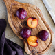 High angle view of fresh purple plum on a textured wooden cutting board. - PhotoDune Item for Sale