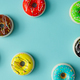 Creative arrangement of colorful donuts on pastel blue background. Minimal food concept. Flat lay. - PhotoDune Item for Sale