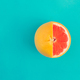 Red grapefruit on bright blue background. Minimal flat lay concept. - PhotoDune Item for Sale