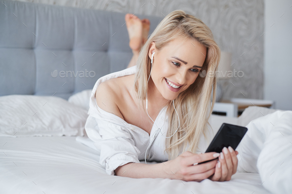 Adorable, smiling blond woman lying in white bed and using a smartphone - Stock Photo - Images