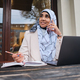 Pretty Arabic businesswoman in hijab happily talking on smartphone while working on laptop on street - PhotoDune Item for Sale
