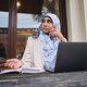 Young Arabic student in hijab confidently talking on smartphone working on laptop on city street - PhotoDune Item for Sale