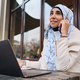 Young attractive Arabic businesswoman in hijab talking on smartphone during work on laptop on street - PhotoDune Item for Sale