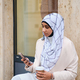Attractive Arabic woman in hijab using smartphone while sitting on city street with coffee to go - PhotoDune Item for Sale