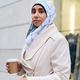 Young casual Arabic woman in hijab walking around street with coffee to go - PhotoDune Item for Sale